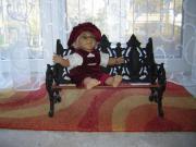 Puppe auf Gußeisensofa
